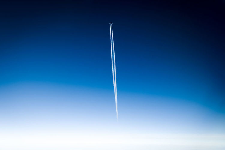 Vapor Trail Blue Cloud - Sky Flying Sky No People Air Vehicle Transportation Mode Of Transportation Motion Airplane Nature Mid-air Low Angle View Day Speed Copy Space on the move Outdoors Plane Blue Background