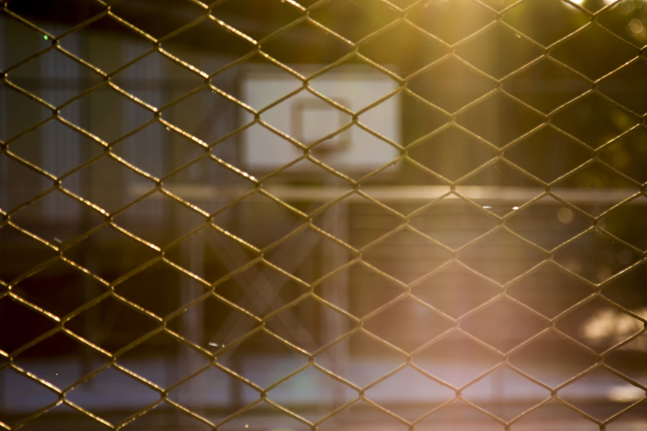 Full Frame Shot Of Chainlink Fence Against Basketball Hoop During Sunset