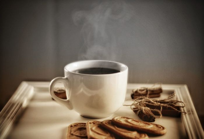 One cup of hot drink, cinnamon, and biscuits perfect treat for a warm winter day during Christmas Beverage Christmas Market New Year Steam Treats Warming Winter Wooden Table Biscuits Cinnamon Coffee Cup Cup Drink Food And Drink Gray Background Hot Drink Indoors  Jolly No People Refreshment Season  Sweet Food Table White Color Wooden