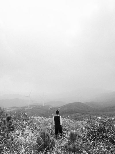 Rear view of man standing on land against sky