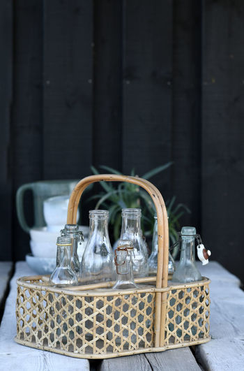 Close-up of bottles in wooden basket on table