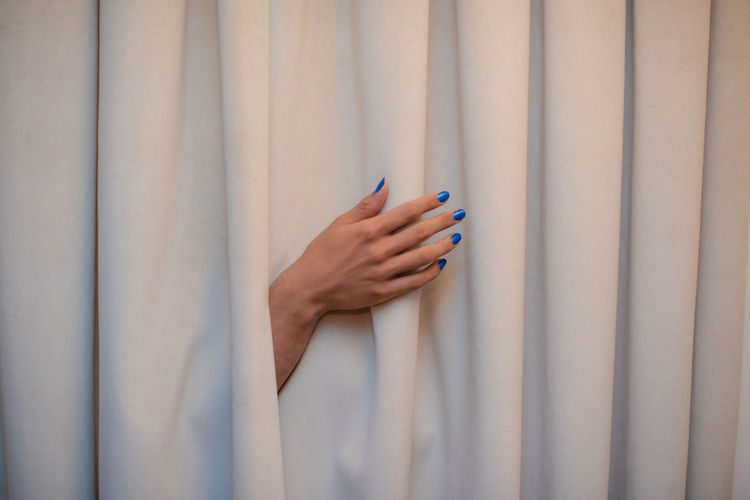Hand protruding from behind curtain