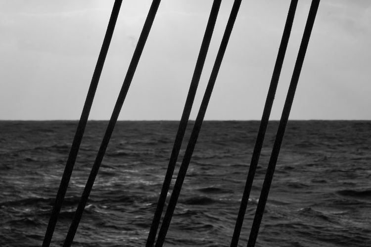 Close-up of sailboats on sea against sky