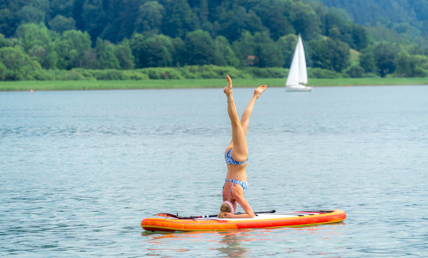 Woman doing headstand on paddleboard in lake