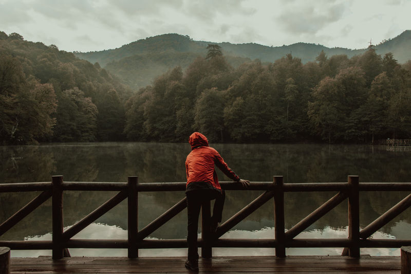 Man standing on railing by lake against mountains
