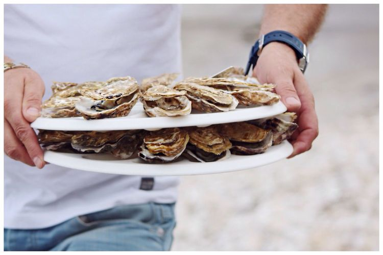 Mid section of a man holding shellfish in plates