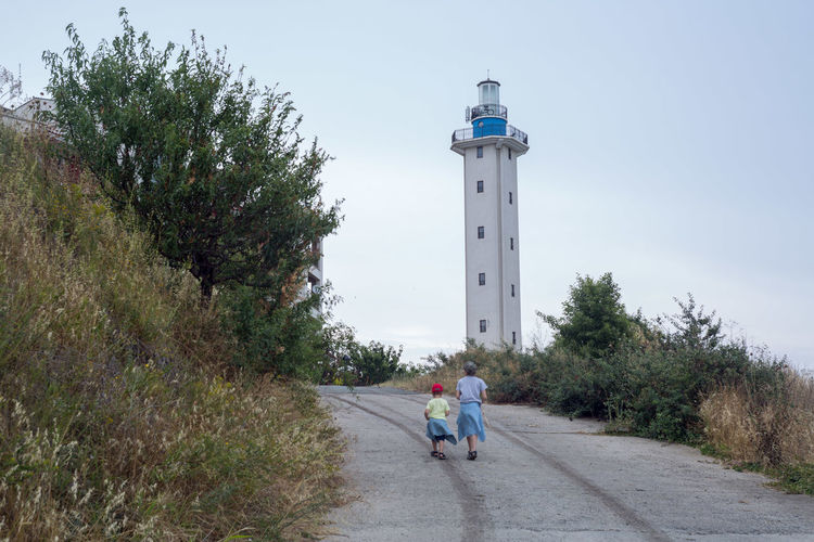 People on footpath by lighthouse against sky