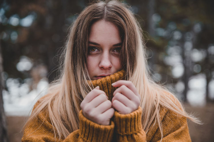 Portrait of young woman wearing sweater standing outdoors during winter