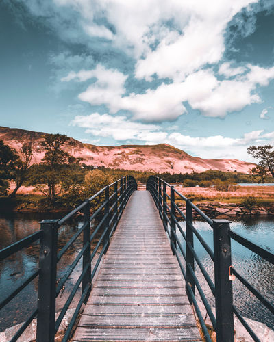 Footbridge leading towards mountains against sky