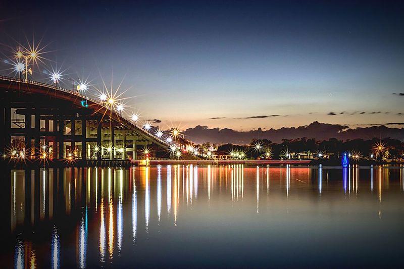 Reflection of illuminated bridge in water at sunset