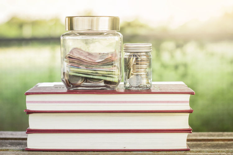 Close-Up Of Currency In Jars On Stacked Books At Table