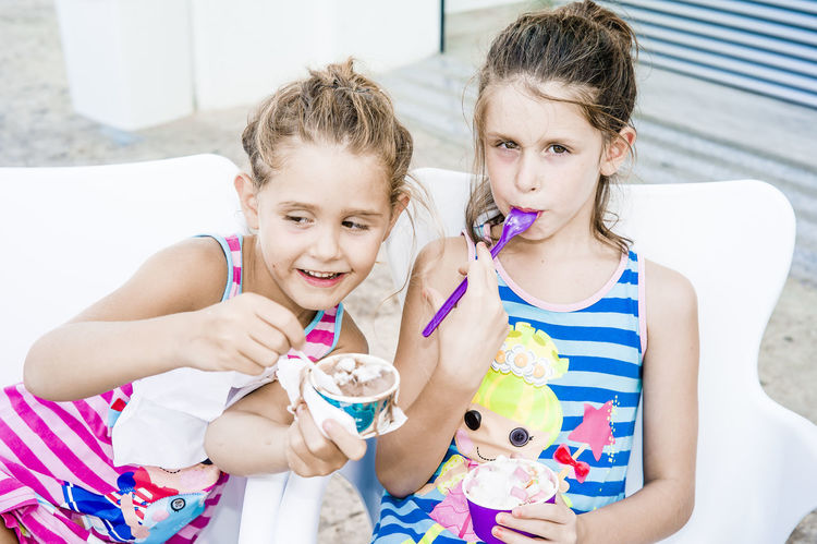 Twins eating ice cream at the beach front ice cream parlour looking out Beach Promenade Casual Clothing Child Childhood Emotion España Family Front View Girl Girls Holding Ice Cream Ice Cream Parlour Innocence Lifestyles Looking At Camera Muliticolor Observing People Outdoors Sibling Sister Smiling Togetherness Twins White Background