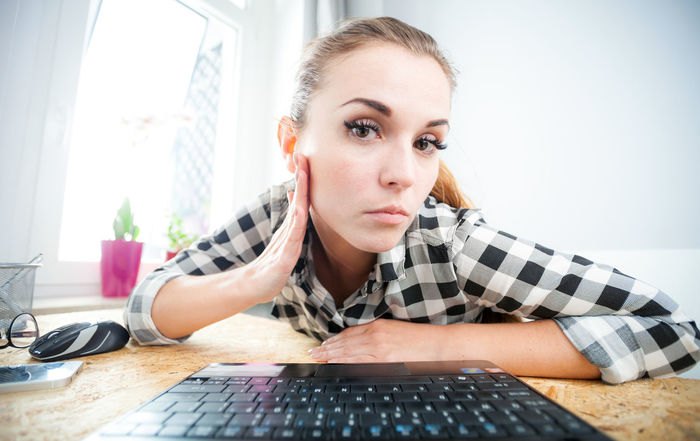 Beauty Casual Clothing Confidence  Domestic Life Focus On Foreground Front View Headshot Home Interior Indoors  Laptop Keyboard Laptop Work Lifestyles Looking At Camera Mirror Person Relaxation Sitting Sofa Table Woman Portrait Wrinkles Young Adult