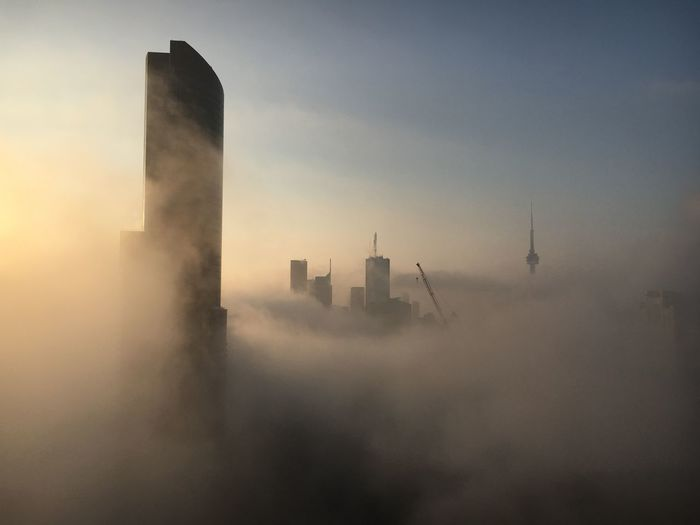 Buildings and cranes in city against sky during foggy weather