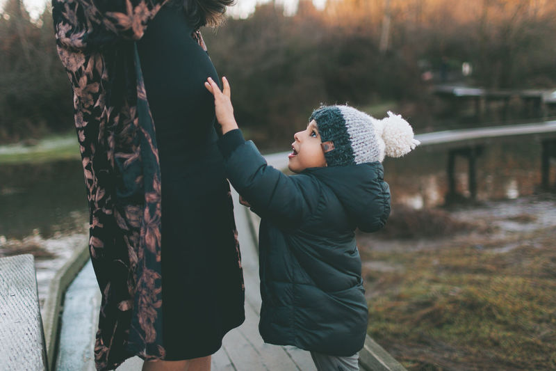 A little boy touching his mothers pregnant belly. Mother Son Woman Child Boy Together Family Outdoors Sunset Love Happy Maternity Pregnant Brother Belly Curious Indian Asian  Diverse Human Connection