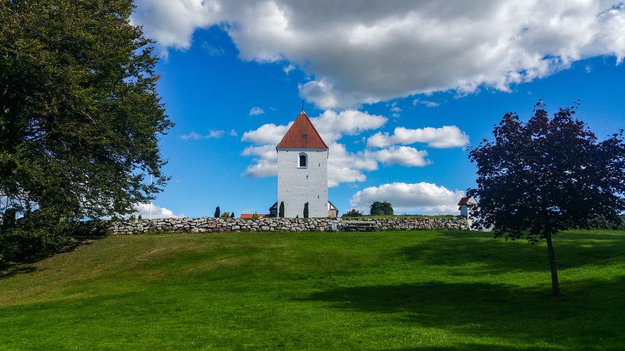 Ullits church by lawn against cloudy sky