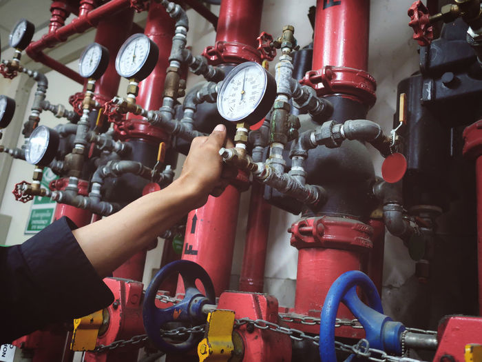 Cropped hand of man holding valve