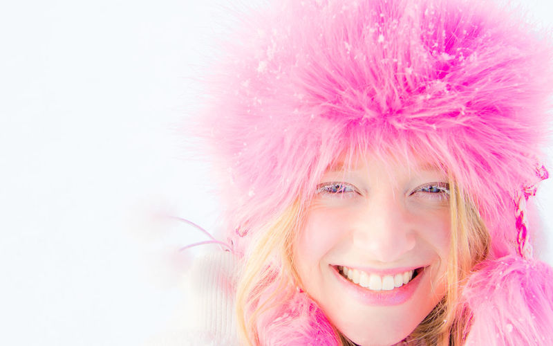Close-Up Portrait Of Smiling Woman Wearing Fur Coat During Winter Against White Background