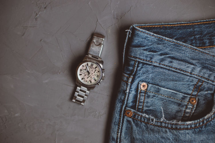 Directly above shot of wristwatch and jeans on gray background