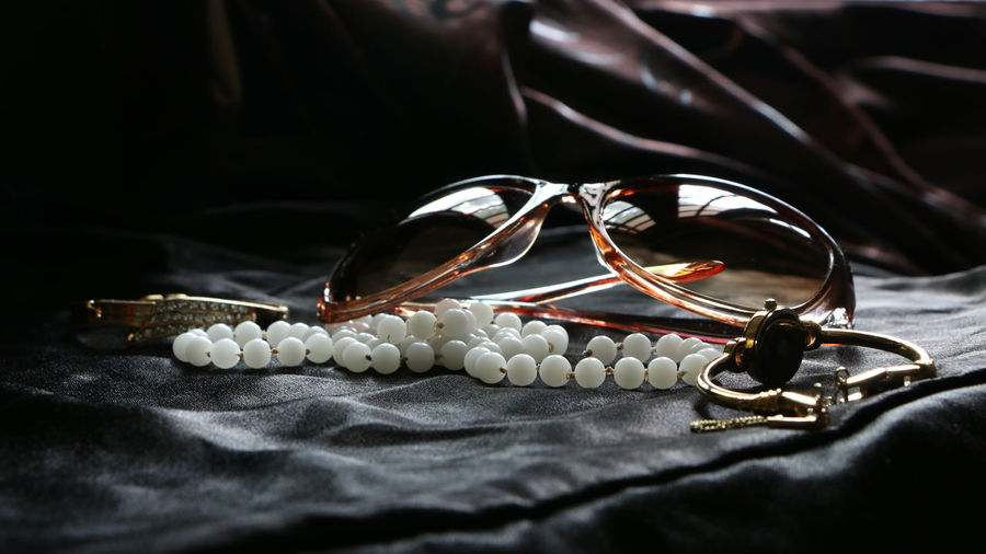 Close-up of pearl necklace with sunglasses and watch on table