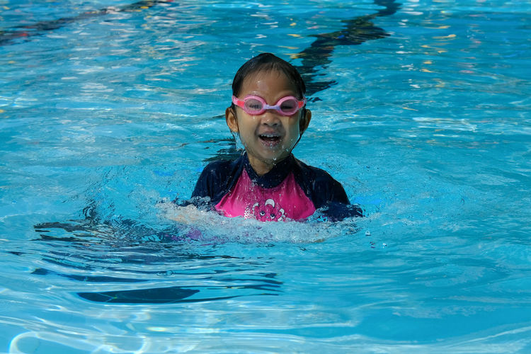 Portrait of cheerful girl swimming in pool