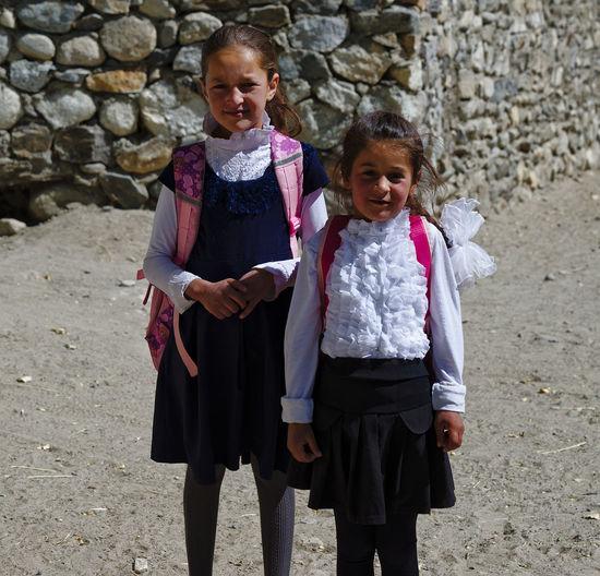 Full length of siblings standing against stone wall
