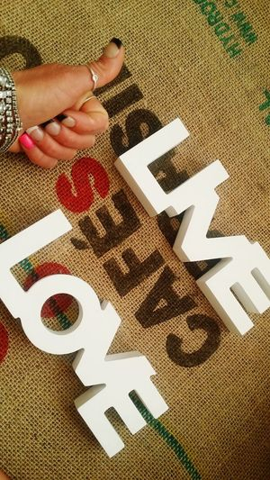 Cropped image of hand gesturing thumbs up by live and love signs on sack
