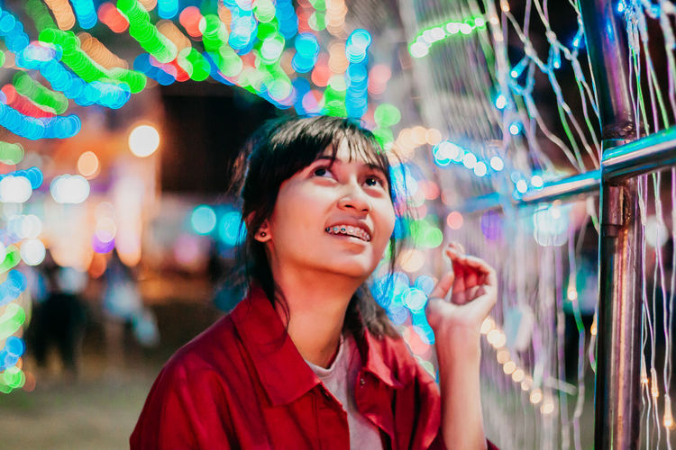 Smiling young woman looking at illuminated multi colored lighting equipment