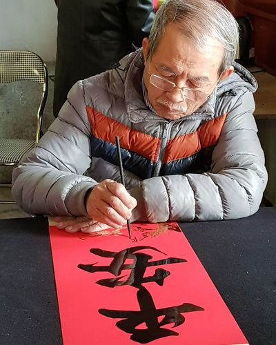 I made the trip in Feb this year. I only found out yesterday that before the viet new year, calligraphers offer their services in the temple and scrolls with blessings in calligraphy are given away, to be displayed in houses. The chinese characters the artist has written says Ping An - meaning Peace. The young tourists frrom Europe and USA must have known this - they were then discussing excitedly which blessing they should ask for. It wasn't free though.. A nominal fee was paid by Ellen. We were just lucky to be there ! Art Calligraphy Calligraphers Chinese Characters Temple Of Literature Temple Of Confucius Hanoi Holiday With Sharon Lsc_hanoi Winter 2018_temple Of Literature_calligrapher Ink Human Hand