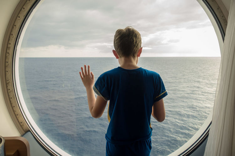 Boy looking at sea against sky