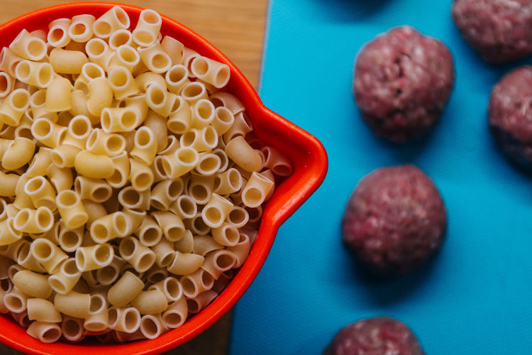 Close-Up Of Raw Pasta In Saucepan By Meatballs On Table