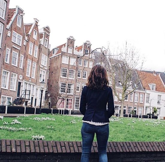 Rear view of woman standing against buildings