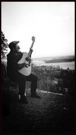 Musician Sam Burrell in Canada playing acoustic Guitar over looking Vancouver city. Monochrome Canada Vancouver Musician