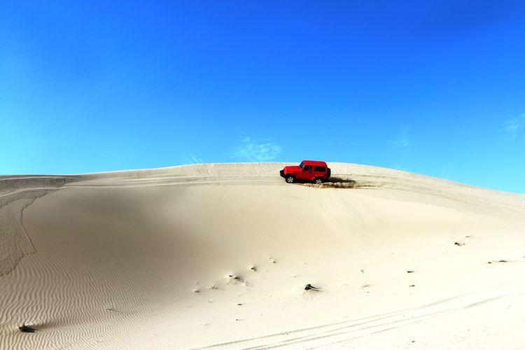 Low angle view of racing car on sand dune