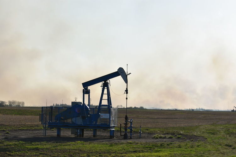 wildfires and oil Alberta Canada Wildfire Smoke Trees No People Field Spring Fireseason Smolder Praries Day Dirt Watching EyeEm Selects Oil Pump Oil Well Manufacturing Equipment Oil Industry Industry Drilling Rig Sky Industrial Equipment Farmland Drill Oil