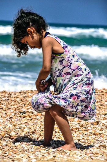 Beach Casual Clothing Childhood Day Enjoyment Focus On Foreground Full Length Innocence Leisure Activity Lifestyles Nature Outdoors Person Playing Relaxation Sea Shore Summer Sunny Vacations Water Weekend Activities Young Adult