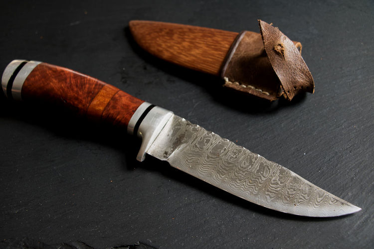 valuable hunting knife with engraving and knife pocket Blade Brown Brown Color Close-up Engraving Engravings Fish Knife Focus On Foreground High Angle View Hobby Knife Hunting Knife Indoors  Kitchen Knife Knife Knife Bag Metal No People Presious Sharp Sharpness Sign Social Issues Still Life Warning Sign Wood - Material