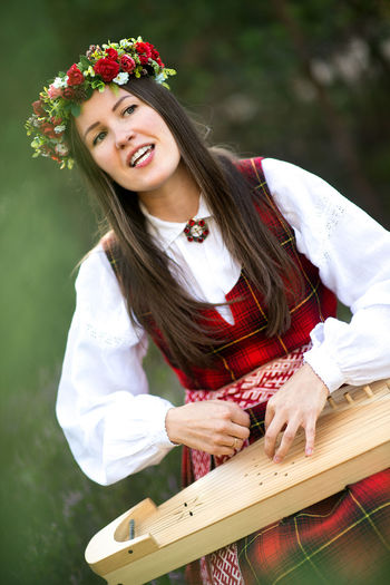 Beautiful latvian girl playing string instrument in the forest Music Beautiful Woman Casual Clothing Day Flower Flower Crown Latvian Latvian Girl Lifestyles Lute Music Is My Life Musical Instrument Musician National Costume One Person Outdoors People Portrait Real People Red Smiling String Instrument Wood - Material Young Adult Young Women