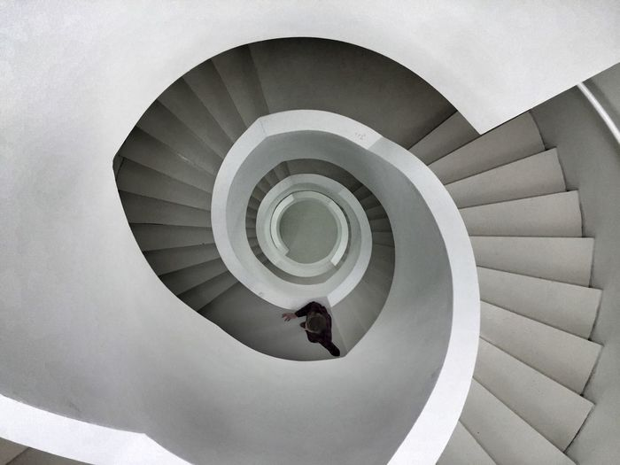 Directly above shot of man climbing a spiral staircase