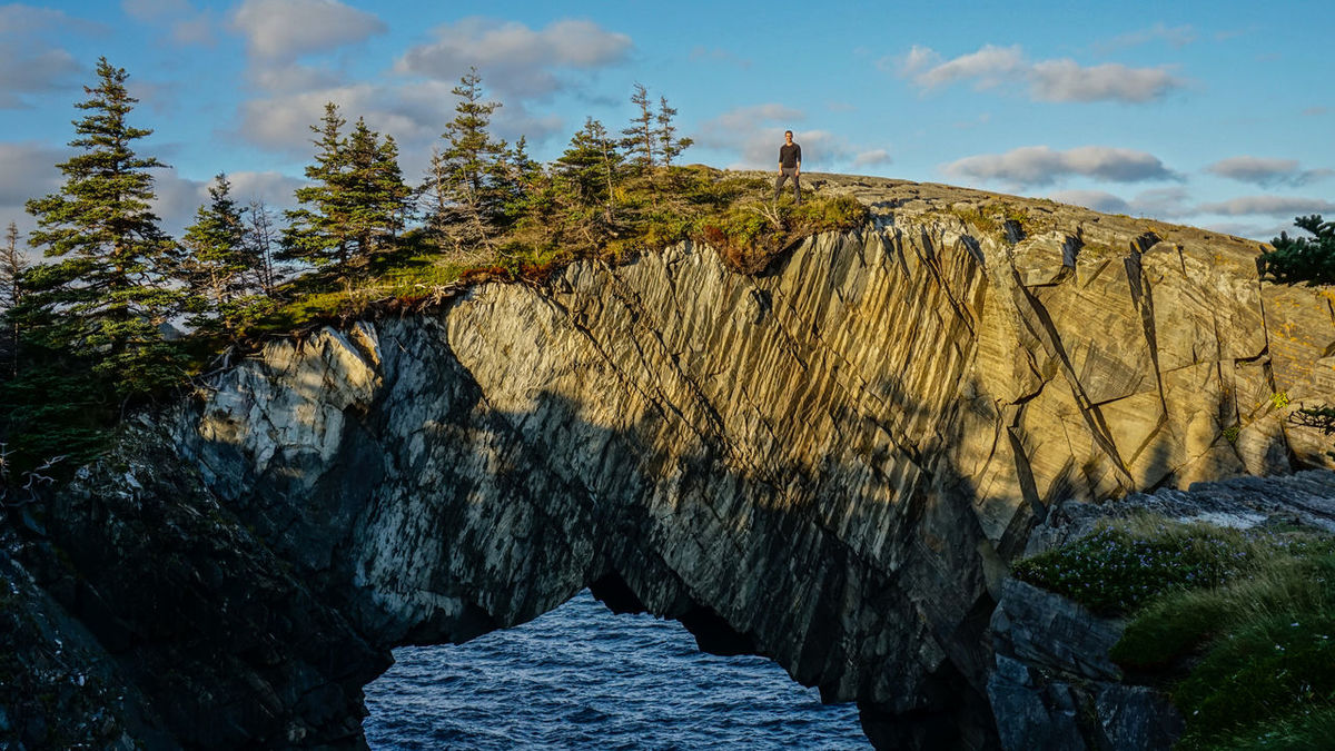 Hiker on top of the Berry Head Arch rock formation on the East Coast Trail hiking trail in Newfoundland, East Canada. Newfoundland Newfoundland, Canada East Coast Trail Ect East Coast Trail Canada Canada Canada Photos Hiking Trekking Hike Walking Camping Nature Landscape Mountain Rock Ocean Sea Backpacking