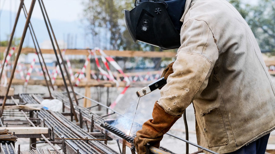 Midsection of welder welding at construction site