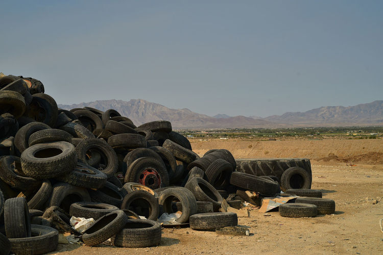 Pile of worn-out black rubber vehicle tires in mojave desert distant mountains pahrump, nevada, usa