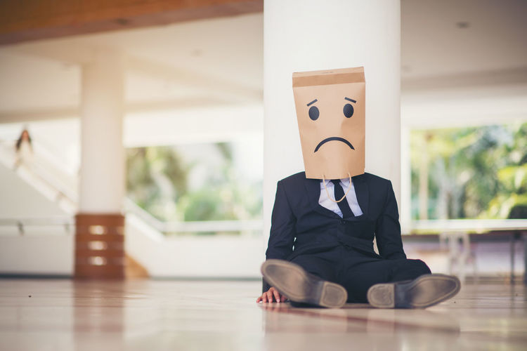 Businessman Wearing Paper Bag Of Sad Face While Sitting On Floor