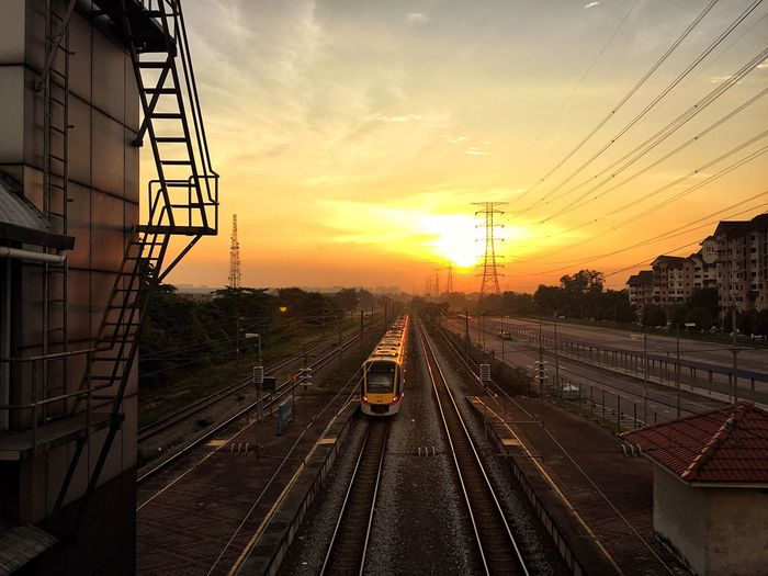 Railroad tracks in city against sky during sunset