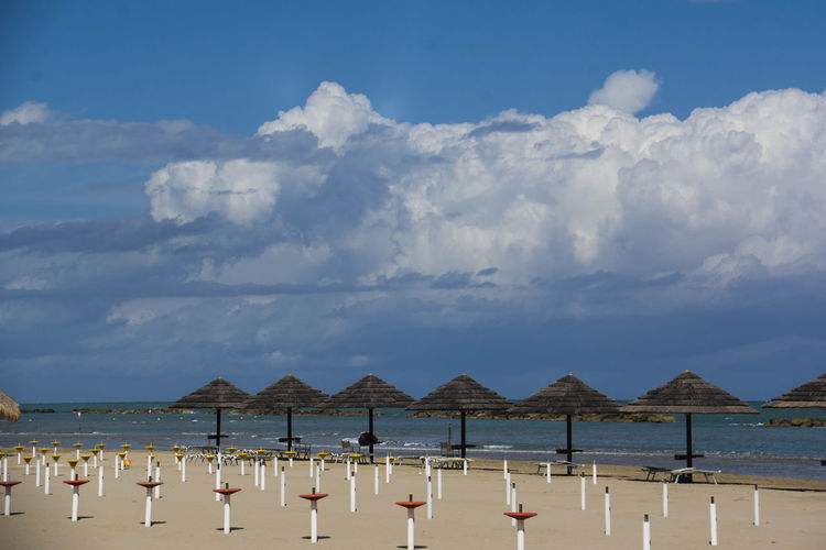 Parasols on shore at beach against cloudy sky