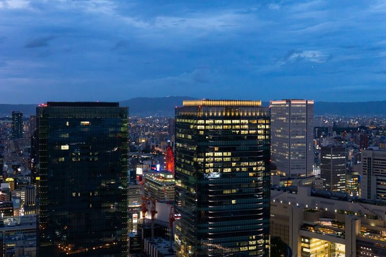 High angle view of illuminated buildings against sky at dusk