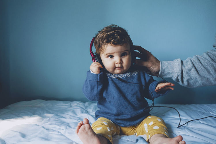 Cute girl listening music on headphones at home