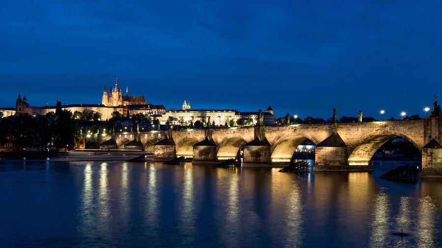 Charles bridge over vltava river against sky in city at dusk