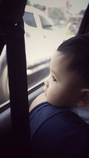 Close-up of boy looking away while sitting in car