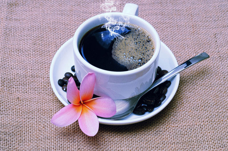 High Angle View Of Black Coffee With Frangipani Coffee Beans On Table